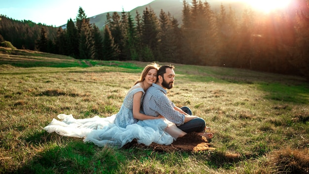 A young couple in the mountains sit on the grass and hug