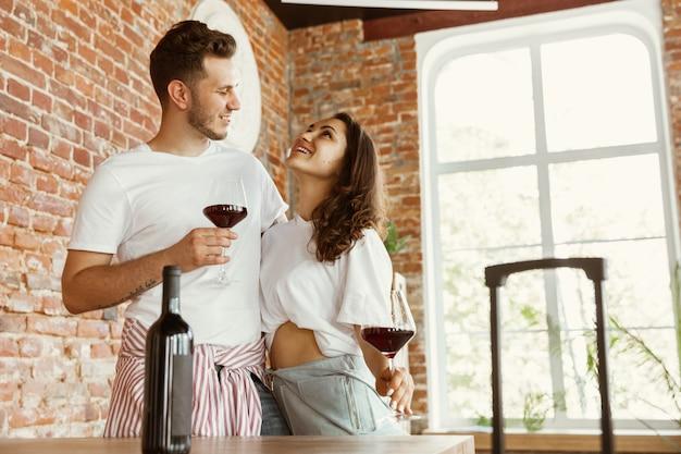 La giovane coppia si è trasferita in una nuova casa o appartamento. bere vino rosso, coccolarsi e rilassarsi dopo la pulizia e il disimballaggio. sii felice e fiducioso. famiglia, trasloco, relazioni, concetto di prima casa.