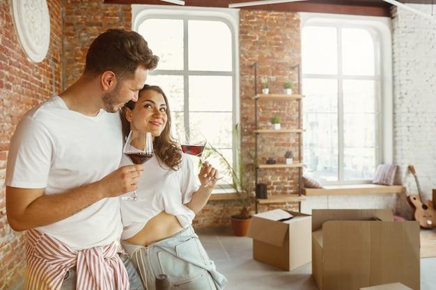 La giovane coppia si è trasferita in una nuova casa o appartamento. bere vino rosso, coccolarsi e rilassarsi dopo la pulizia e il disimballaggio