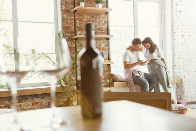 Young couple moved to a new house or apartment. drinking red wine, using smartphone and relaxing after cleaning and unpacking. look happy and confident. family, moving, relations concept.