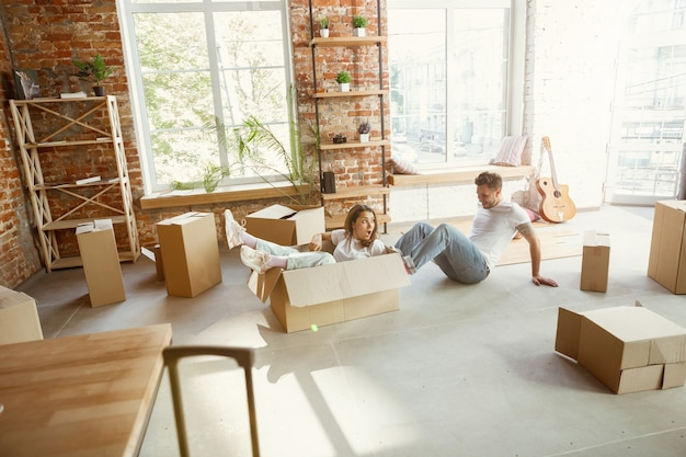 La giovane coppia si è trasferita in una nuova casa o appartamento. divertirsi con le scatole di cartone, rilassarsi dopo la pulizia e il disimballaggio nel giorno del trasloco