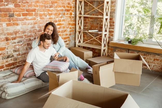 La giovane coppia si è trasferita in una nuova casa o appartamento. stare sdraiati, accarezzare, abbracciare, divertirsi in un giorno traslocato. sembri felice, sognante e fiducioso. famiglia, trasloco, relazioni, concetto di prima casa.