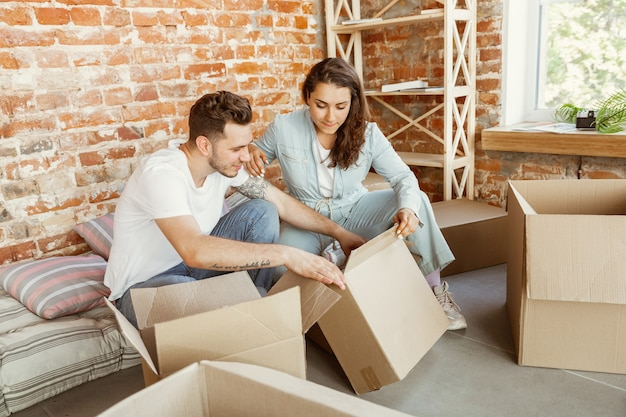 Young couple moved to a new house or apartment. unpacking cardboard boxes together, having fun at moved day. look happy, dreamful and confident. family, moving, relations, first home concept.