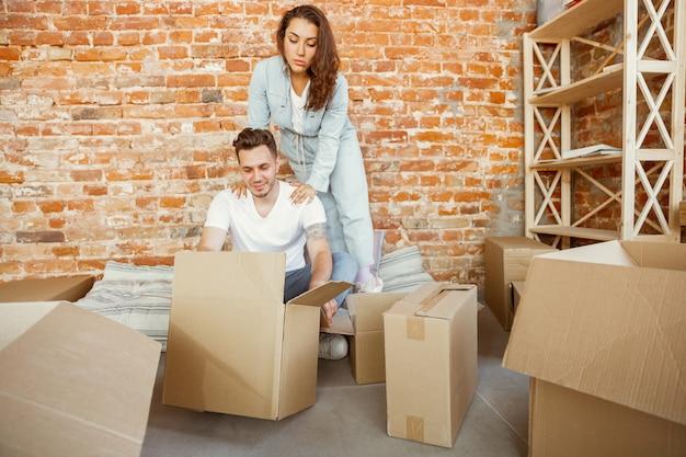 La giovane coppia si è trasferita in una nuova casa o appartamento. disimballare insieme scatole di cartone, divertendosi al trasloco. sembri felice, sognante e fiducioso. famiglia, trasloco, relazioni, concetto di prima casa.