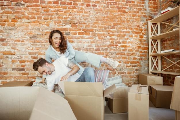 La giovane coppia si è trasferita in una nuova casa o appartamento. disimballare insieme scatole di cartone divertendosi al trasloco