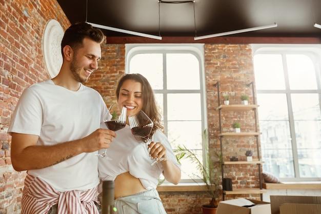 Молодая пара переехала в новый дом или квартиру. пить красное вино, обниматься и расслабляться после уборки и распаковки. выгляди счастливым и уверенным. семья, переезд, отношения, концепция первого дома.