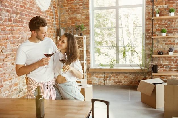 若いカップルは新しい家やアパートに引っ越しました。赤ワインを飲み、掃除と開梱の後に抱きしめてリラックスします。幸せで自信を持って見えます。家族、引っ越し、関係、最初の家のコンセプト。