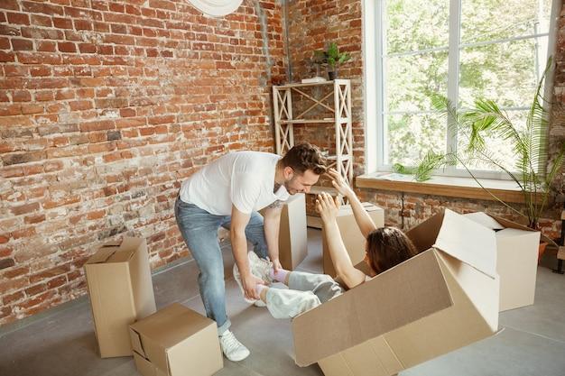 Молодая пара переехала в новый дом или квартиру. развлекаемся с картонными коробками, отдыхаем после уборки и распаковываем вещи в перенесенный день. выгляди счастливым. семья, переезд, отношения, концепция первого дома.