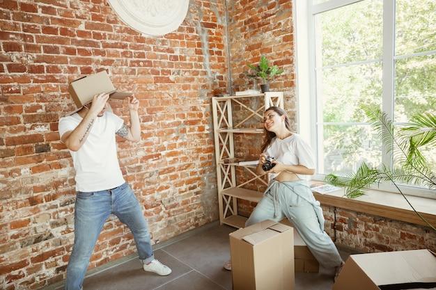 젊은 부부는 새 집이나 아파트로 이사했습니다. 골판지 상자를 가지고 즐거운 시간을 보내고, 청소 후 휴식을 취하고 이사 한 날에 포장을 풀었습니다. 행복해 보인다. 가족, 이사, 관계, 첫 번째 가정 개념.