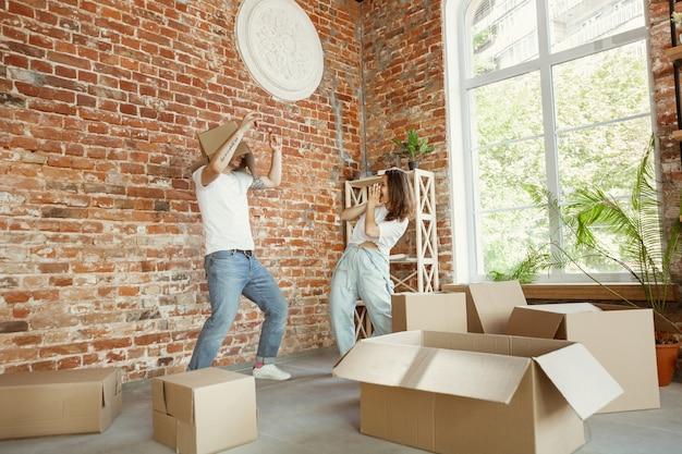 若いカップルは新しい家やアパートに引っ越しました。段ボール箱を楽しんだり、引っ越しの日に掃除や開梱をした後はリラックス。幸せそうに見えます。家族、引っ越し、関係、最初の家のコンセプト。