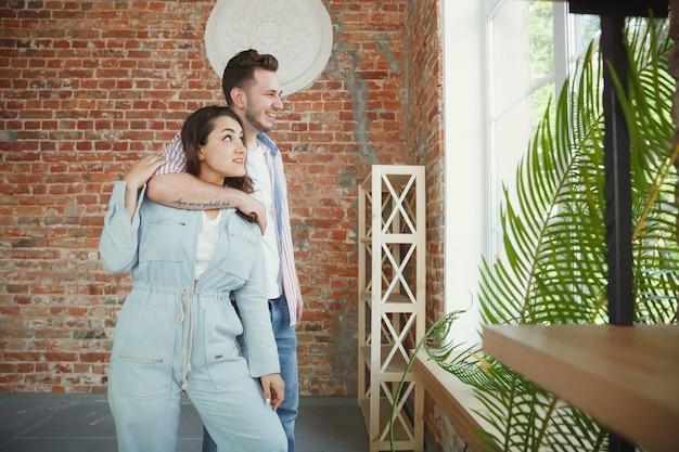 若いカップルは新しい家やアパートに引っ越しました。幸せで自信を持って見えます。家族、引っ越し、関係、最初の家のコンセプト。将来の修理を考え、掃除や開梱後にリラックス。