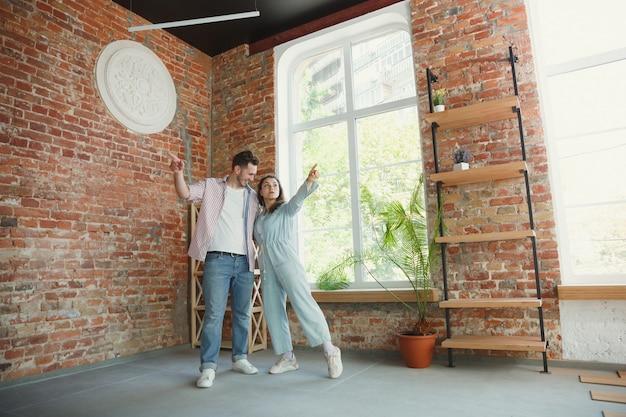 若いカップルは新しい家やアパートに引っ越しました。幸せで自信を持って見えます。家族、引っ越し、関係、最初の家のコンセプト。将来の修理を考え、掃除や開梱後のリラックス。