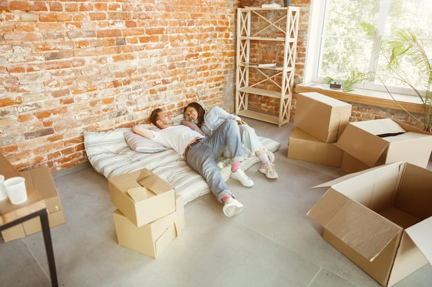 Молодая пара переехала в новый дом или квартиру. лежат вместе, отдыхают после уборки и распаковывают вещи в перенесенный день. выглядите счастливым, мечтательным и уверенным в себе. семья, переезд, отношения, концепция первого дома.