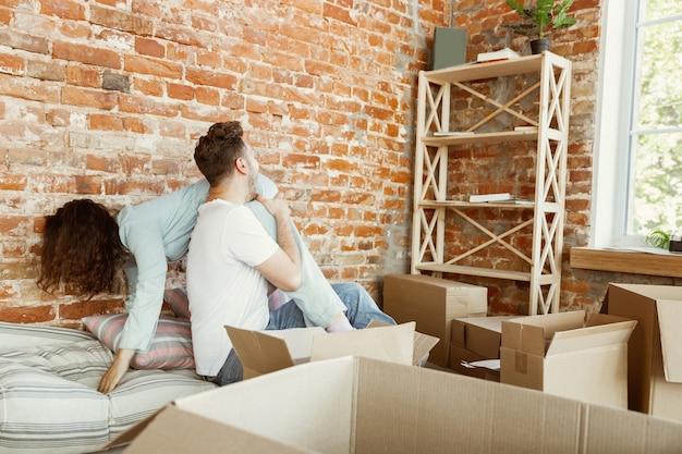 Молодая пара переехала в новый дом или квартиру. вместе распаковываем картонные коробки, развлекаемся перенесенным днем. выглядите счастливым, мечтательным и уверенным в себе. семья, переезд, отношения, концепция первого дома.