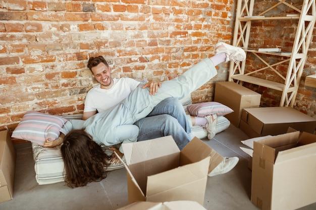 젊은 부부는 새 집이나 아파트로 이사했습니다. 골판지 상자를 함께 풀고 이사 한 날을 즐겁게 보내세요. 행복하고 꿈꾸며 자신감있게 보입니다. 가족, 이사, 관계, 첫 번째 가정 개념.