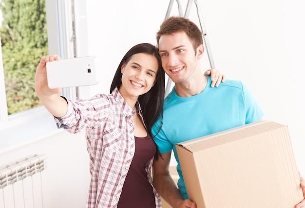 Молодая пара, перемещая коробки в новом доме
