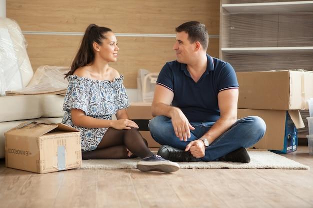 새 집으로 이사하는 젊은 부부. 남자와 여자가 깨지기 쉬운 물건을 언박싱합니다.