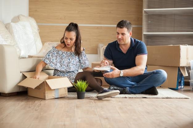 Молодая пара переезжает в новый дом. мужчина и женщина распаковывают хрупкие вещи.