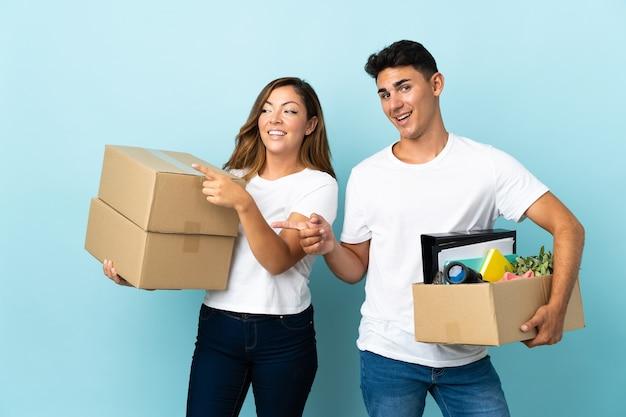 Молодая пара переезжает в новый дом среди коробок на синем, указывая пальцем в сторону в боковом положении
