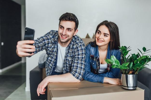 Молодая пара переезда в новый дом и принимая селфи. делаем селфи со смартфоном в новой квартире