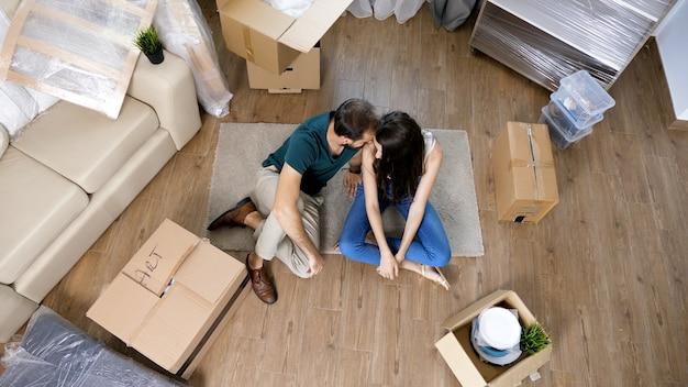 젊은 부부는 새 집으로 이사하고 판지 상자를 풀고 있습니다. 이사 거의 다 갑니다.