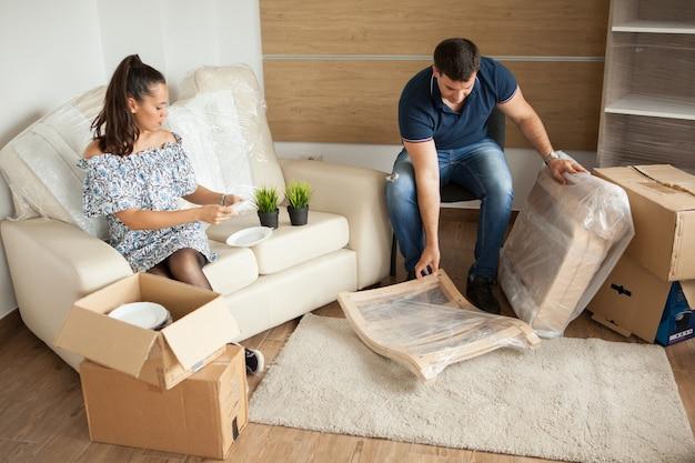 젊은 부부 새 집으로 이사하고 판지 상자를 풀고 이사를 거의 마쳤습니다.