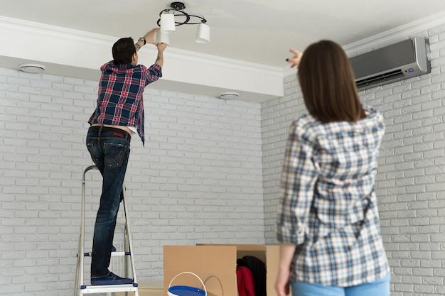若いカップルが新しい家に移動、電球を変更します。
