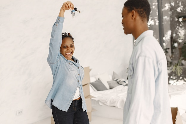 若いカップルが一緒に新しい家に移動します。段ボール箱とアフリカ系アメリカ人のカップル。女性はキーを押したままにします。