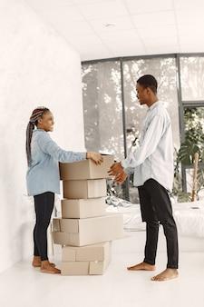 若いカップルが一緒に新しい家に移動します。段ボール箱とアフリカ系アメリカ人のカップル。