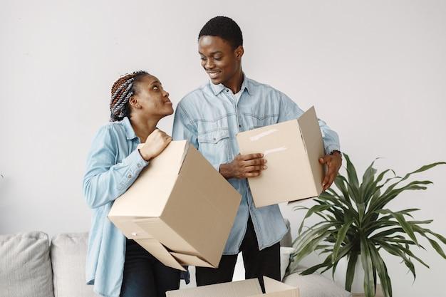Молодая пара вместе переезжает в новый дом. афро-американская пара с картонными коробками.