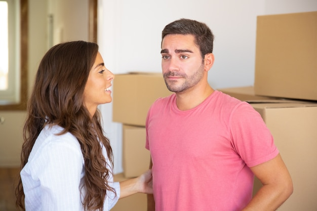 Young couple moving into new apartment, standing among carton boxes and discussing unpacking
