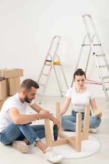 Young couple moving into new house sitting on floor and assembling coffee table together