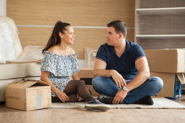 Young couple moving in a new home.man and woman unboxing fragile stuff.