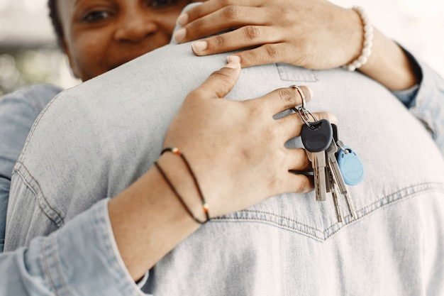 Young couple moving in to new home together. african american couple with cardboard boxes. woman hold keys.