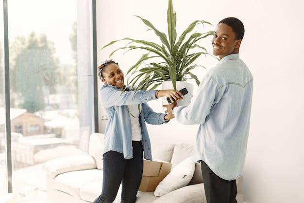 Giovani coppie che si trasferiscono insieme nella nuova casa. coppia afro-americana con scatole di cartone.