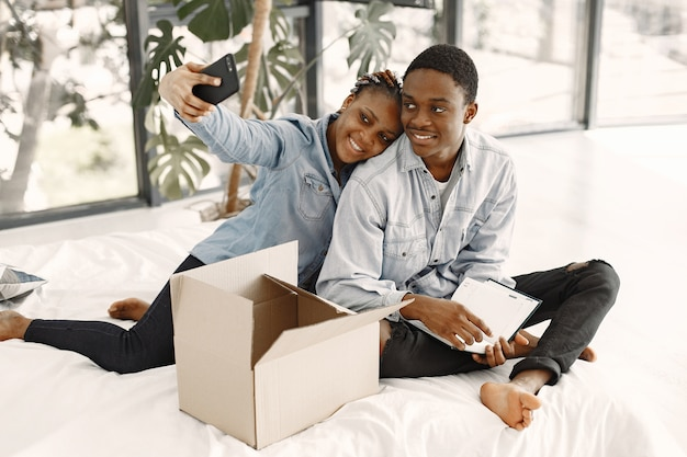 Young couple moving in to new home together. african american couple with cardboard boxes.