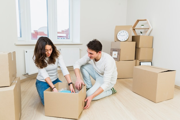 Young couple moving to new place sitting near cardboard box unpacking dishes