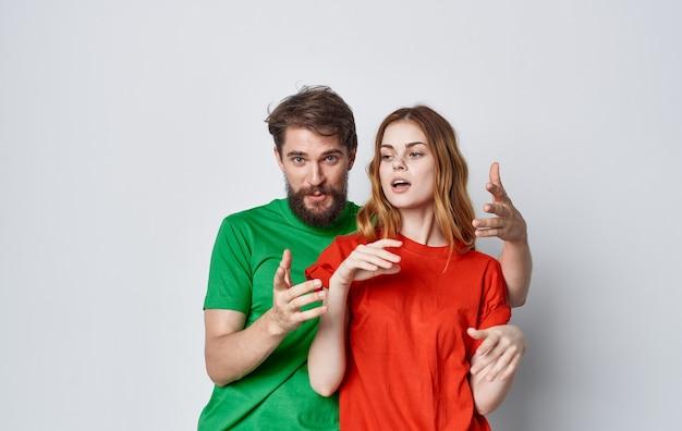 若いカップルの色とりどりのtシャツライフスタイルモックアップスタジオ。