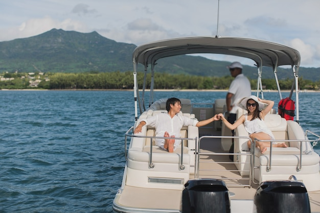 Young couple navigating on a yacht in indian ocean. handsome man and woman on deck of yacht lie on soft chair