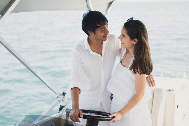 Young couple navigating on a yacht in indian ocean