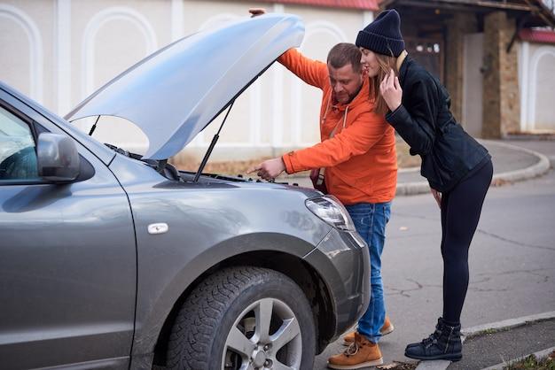 道路上のフードが開いている車の近くの若いカップル。