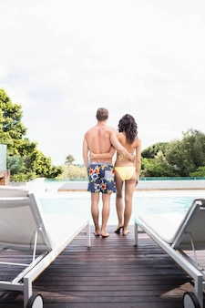 Young couple near swimming pool enjoying holiday