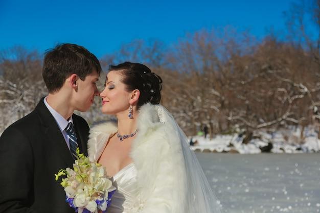 Молодая пара молодоженов гуляет в зимнем лесу в снегу. жених и невеста обнимаются в парке зимой. красивые мужчина и женщина в свадебных нарядах среди сосен.