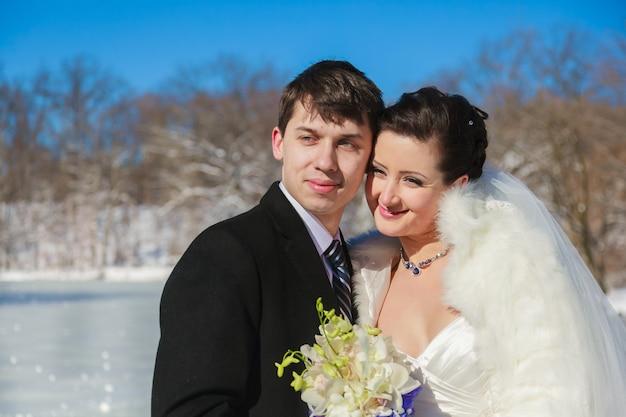雪の中で冬の森を歩く若いカップルの新婚夫婦。冬に公園で抱き締める新郎新婦。彼らの結婚式の服を着た美しい男性と女性は松の中にあります。