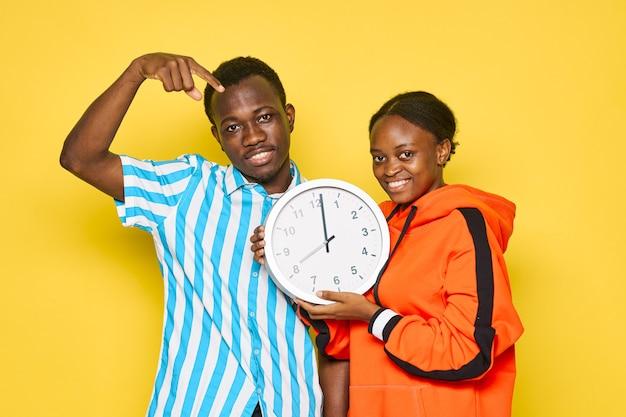 노란색 손에 시계를 들고 아프리카 외모의 젊은 부부