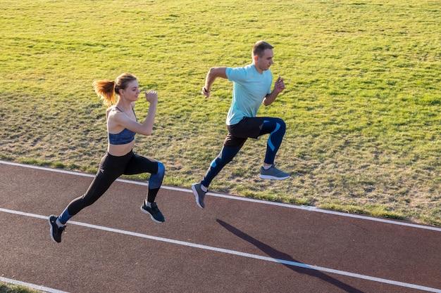 フィットスポーツマンの男の子と女の子の実行の若いカップル