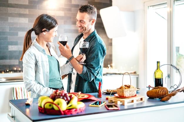 집 주방에서 적포도주를 굽는 젊은 연인 - 희년 기념일에 함께 환호하는 아페리티프 시간을 즐기는 행복한 밀레니얼 세대 - 밝은 천연 필터에 대한 진정한 청소년 사랑 개념