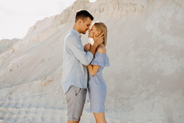 男性と女性の若いカップルが、屋外でキスしようとしています。