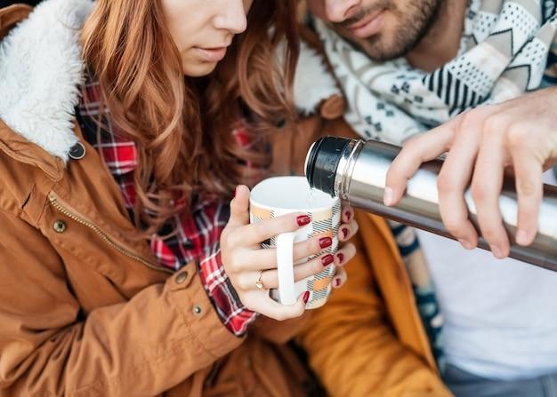 男性と女性の若いカップル、冬の日に熱いお茶を飲みます。
