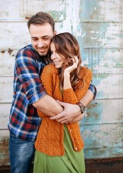 Молодая пара мужчина и женщина обнимаются, стоя у металлической стены